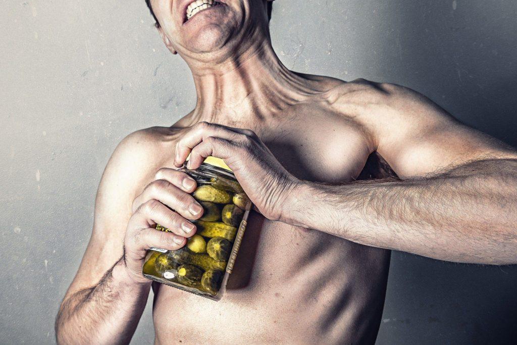 Vyčerpané tělo pocovid 19 se pokouší otevřít lahev okurek